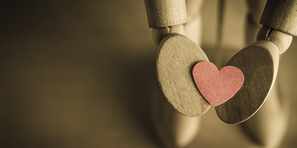 A wooden hand holding out a heart, representing the love between inbound and paid advertising